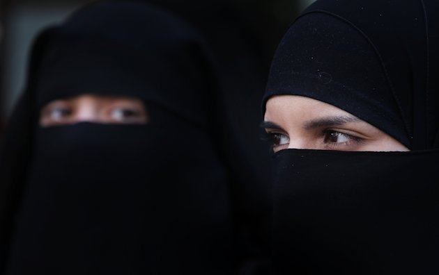Two women wearing Islamic niqab veils stand outside the French Embassy in London, England. (Getty)