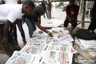 Men read newspapers on a street with headlines about Ebola Virus killing a Liberian in Lagos, Nigeria. Saturday, July 26, 2014. An Ebola outbreak that has left more than 660 people dead across West Africa has spread to the continent's most populous nation after a Liberian man with a high fever vomited aboard an airplane to Nigeria and then died there, officials said Friday. The 40-year-old man had recently lost his sister to Ebola in Liberia, health officials there said. It was not immediately clear how he managed to board a flight, but he was moved into an isolation ward upon arrival in Nigeria on Tuesday and died on Friday. (AP Photo/Sunday Alamba)