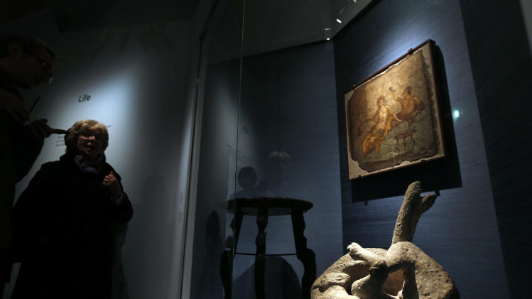 A cast of a dog, which was made by filling plaster in the void left by its body, found in Pompeii is seen, bottom right, among artifacts found in the destroyed city, during a photo call for the upcoming exhibition entitled 'Life and death Pompeii and Herculaneum', at the British Museum in central London, Tuesday, March 26, 2013. The exhibition about the two Roman cities, buried by a catastrophic volcanic eruption of Mount Vezuvius in 79 AD, will run at the museum from March 28 to Sept. 29, 2013. (AP Photo/Lefteris Pitarakis)