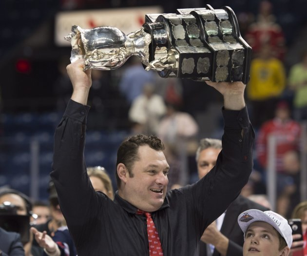 Oshawa Generals head coach D.J. Smith raises the Memorial Cup trophy after they won the tournament 2-1 in overtime against the Kelowna Rockets Sunday, May 31, 2015 at the Memorial Cup final in Quebec City. (Jacques Boissinot/The Canadian Press via AP) MANDATORY CREDIT
