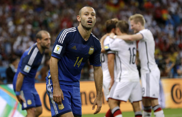 Argentina's Javier Mascherano reacts as German players celebrate scoring the opening goal during the World Cup final soccer match between Germany and Argentina at the Maracana Stadium in Rio de Janeir