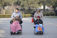 Two elderly people are seen on their wheelchairs at a park in Beijing, on December 11, 2012. China's elderly face increasing uncertainty three decades since the one-child policy took hold, with no real social safety net, the law has left four grandparents and two parents with one caretaker for old age -- and bereaved families with none