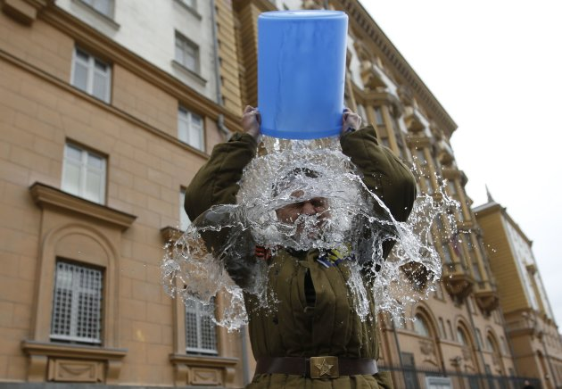 Alexei Didenko, a deputy for the Russian State Duma, dumps a bucket of cold water on himself. (Reuters)