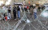 The damaged windshield of a minibus at the site of a blast in the central Midan district of Damascus. Tens of thousands of people protested across Syria as a deadly suicide bombing rocked the capital, killing 11 and fuelling growing scepticism over the prospects of a UN-backed peace plan