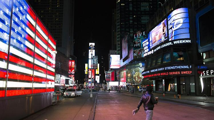 A lone pedestrian walks through an empty Times Square early, Monday, Oct. 29, 2012, in New York. Hurricane Sandy continued on its path Monday, forcing the shutdown of mass transit, schools and financial markets, sending coastal residents fleeing, and threatening a dangerous mix of high winds and soaking rain. (AP Photo/ John Minchillo)