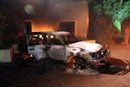 A vehicle and surrounding buildings smoulder after they were set on fire inside the US consulate compound in Benghazi late on September 11. America's ambassador to Libya and three officials were killed when a mob attacked the US consulate to protest a film deemed offensive to Islam, an official said Wednesday
