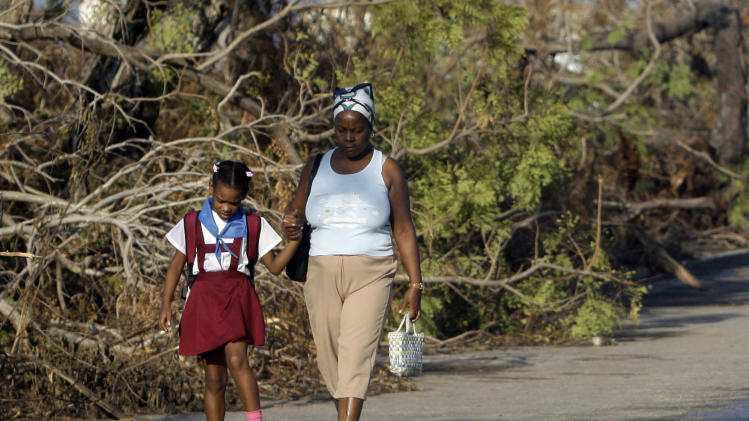 A student walks to school past trees that fell during the passing of Hurricane Sandy in Santiago de Cuba, Cuba, Monday, Nov. 5, 2012.  Classes resumed Monday in a sign of some return to normalcy. But more than 100 schools remain shuttered due to storm damage.  (AP Photo/Ismael Francisco, Cubadebate)