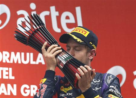 Red Bull Formula One driver Vettel kisses his trophy on the podium after winning the Indian F1 Grand Prix at the Buddh International Circuit in Greater Noida