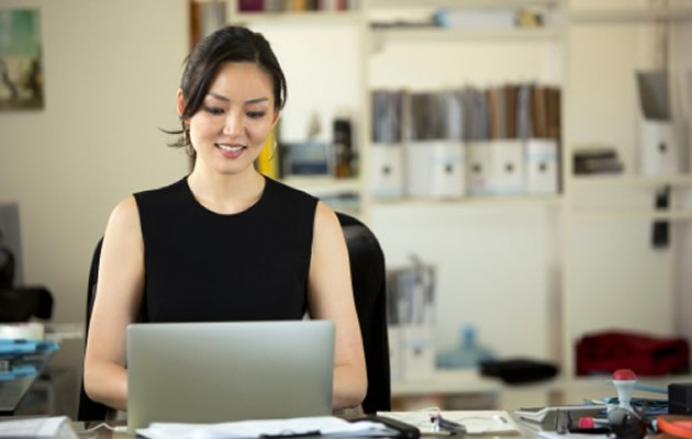 Asian woman working at an office. (Getty Images)