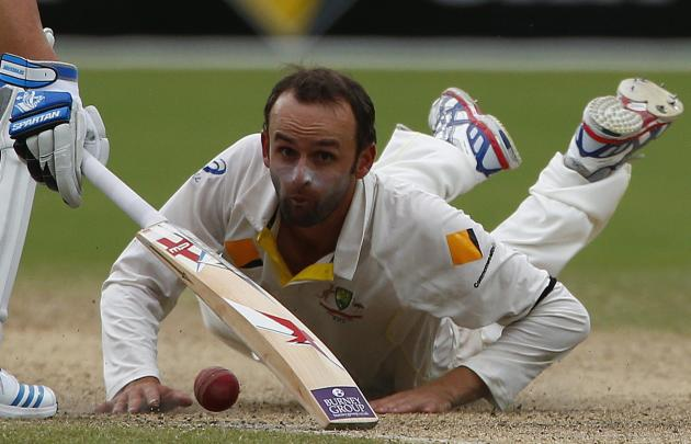 Australia's Lyon looks at the ball after a miss fielding hit by England's Stokes during the fourth day's play in the second Ashes cricket test at the Adelaide Oval
