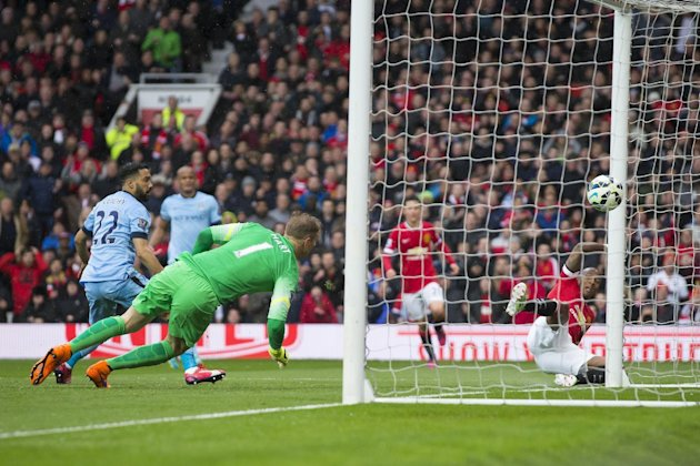 Manchester United's Ashley Young, right, scores past Manchester City's goalkeeper Joe Hart during the English Premier League soccer match between Manchester United and Manchester City at Old Trafford Stadium, Manchester, England, Sunday, April 12, 2015. (AP Photo/Jon Super)