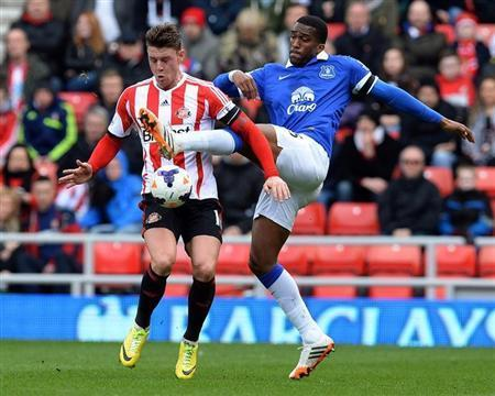 Sunderland's Wickham challenged by Everton's Distin during their English Premier League soccer match at the Stadium of Light in Sunderland