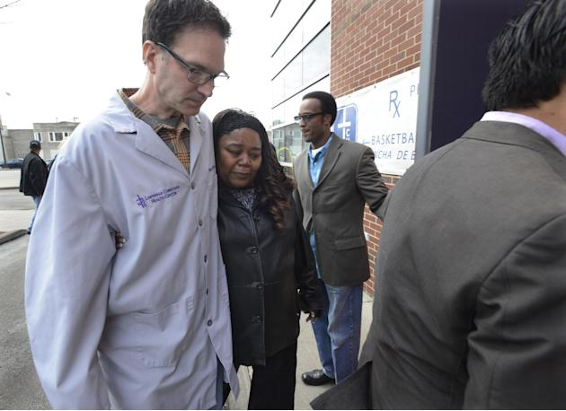 Mourners walk into the Lawndale Christian Health Center after a press conference addressing the death of Dr. Jerry Umanos, a pediatrician at the center in Chicago, Thursday, April 24, 2014. Umanos was