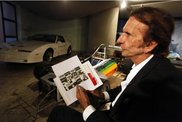 Former Brazilian Formula One driver Emerson Fittipaldi holds a picture of Ayrton Senna during an interview with Reuters in Sao Paulo