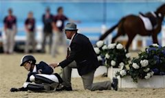 Hwang Woojin, of South Korea, is checked on by an official after getting bucked off his horse Shearwater Oscar, in the equestrian show jumping stage