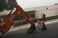 A policeman stands next to a bulldozer removing the security barriers in front of the U.S. embassy in New Delhi December 17, 2013. REUTERS/Adnan Abidi