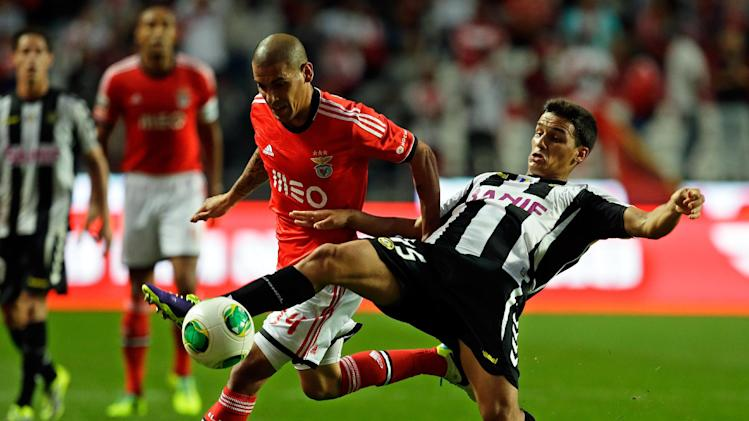 Benfica's Maxi Pereira, from Uruguay, fights for the ball with Nacional's Jota, right, during their Portuguese league soccer match Sunday, Oct. 27, 2013, at Benfica's Luz stadium in Lisbon