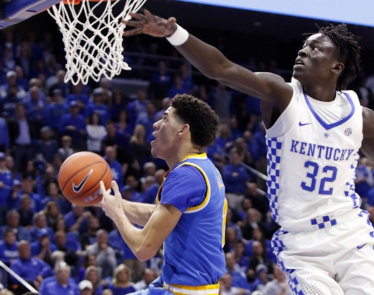 UCLA's Lonzo Ball, left, shoots while defended by Kentucky's Wenyen Gabriel (32) during the first half of an NCAA college basketball game, Saturday, Dec. 3, 2016, in Lexington, Ky. UCLA upset No. 1 Kentucky 97-92. (AP Photo/James Crisp)