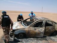 A photo released by the official Syrian Arab News Agency (SANA) shows UN observers inspecting a burnt car in Deir Ezzor. Syrian troops have attacked a central rebel bastion, with dozens reportedly killed across the country, as the EU slaps fresh sanctions on Damascus