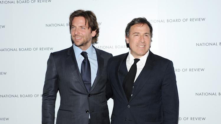 "FILE - This Jan. 8, 2013 file photo shows Bradley Cooper, left, and writer-director David O. Russell, at the National Board of Review Awards gala in New York. A manhunt for a suspect in the Boston Marathon bombing is causing filming on David O. Russell's film ""American Hustle"" to be suspended. Sony spokesman Steve Elzer said Friday that the film's producers are heeding official requests to remain indoors as the massive manhunt Friday virtually shut down the city and some suburbs. ""American Hustle,"" about an FBI sting operation in the late '70s, stars Christian Bale, Amy Adams and Bradley Cooper. (Photo by Evan Agostini/Invision/AP, file)"