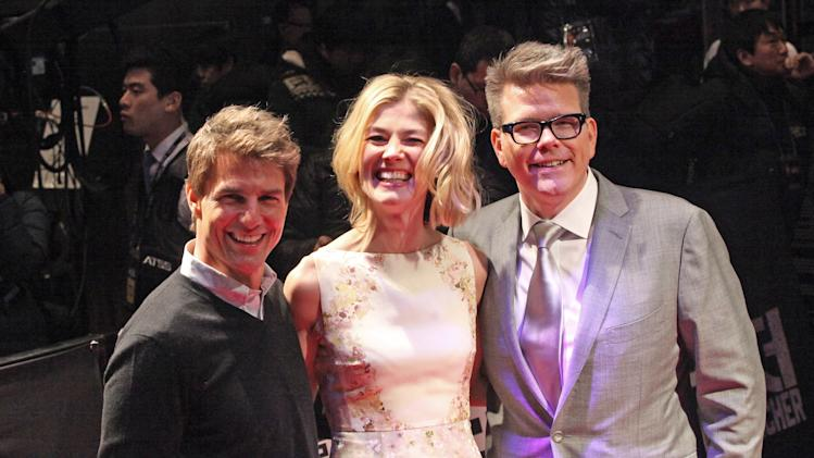 "U.S. actor Tom Cruise, left, British actress Rosamund Pike and director Christopher McQuarrie, right, pose for photographers before a premiere of their new movie ""Jack Reacher"" at the Busan Cinema Center in Busan, South Korea, Thursday, Jan. 10, 2013. (AP Photo/Ahn Young-joon)"