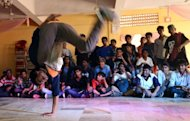 A dancer performs in a competition organised by the SlumGods, a group of b-boy dancers, in Mumbai on November 25, 2012. The SlumGods have inspired hundreds of urban Indian youngsters to try their hands at b-boying, a cheap and funky combination of exercise and self-expression
