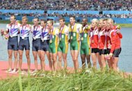 South Africa's (centre), Great Britain's (left) and Denmark's teams pose on the podium after receiving their gold, silver and bronze medals won in the men's lightweight four final A of the rowing event during the London 2012 Olympic Games, at Eton Dorney Rowing Centre, west of London