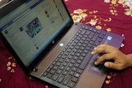 A Bangladeshi woman logs onto social networking website Facebook on her laptop in Dhaka on May 15, 2012. Bangladesh has formed a fast-track court to try cyber criminals after a spike in crimes involving mobile phones and social networking sites such as Facebook, an official said Thursday