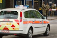 "A police car is parked outside the Royal Artillary Barracks, Headquarters Woolwich Station in Woolwich, east London, on May 22, 2013. British police shot and wounded two men after a man thought to be a serving soldier was killed outside a London barracks, in an attack Prime Minister David Cameron called ""truly shocking""."