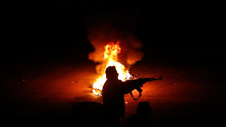 FILE - A Syrian rebel stands next to a flaming tire while firing at a Syrian army checkpoint in a suburb of Damascus, Syria, on Saturday, March 17, 2012. (AP Photo/File)