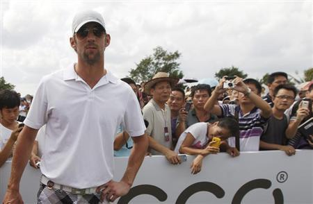 Fans look at and take photos of U.S. Olympic swimmer Michael Phelps during the first round of the Mission Hills World Celebrity Pro-Am golf tournament in Haikou