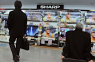 This file photo shows customers watching television sets under a Sharp logo at an electronics shop in Tokyo, in February. Shares in Sharp jumped on Friday on a report the embattled electronics maker may get a cash injection of more than $380 million from US chip giant Intel