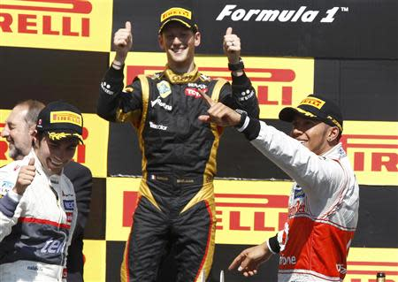 McLaren Formula One driver Hamilton, Lotus F1's Grosjean and Sauber's Perez celebrate during the podium ceremony following the Canadian F1 Grand Prix at the Circuit Gilles Villeneuve in Montreal