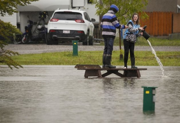A teenager pours water out of her boot after wading through flood waters in a park in Claresholm, Alta.