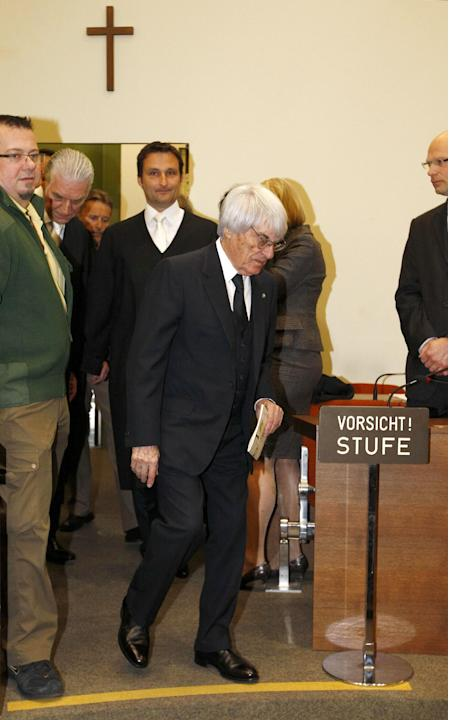 F1 CEO Bernie Ecclestone passes by a sign 'mind the step' as he arrives in the court in Munich, southern Germany, Thursday, April 24, 2014. Ecclestone is charged with bribery and incitement to