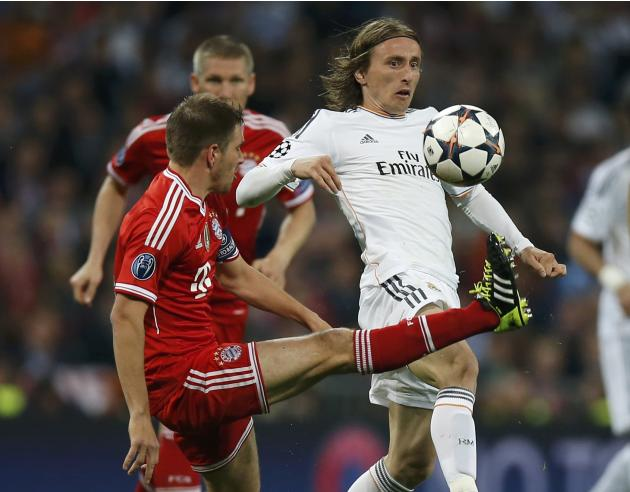 Real Madrid's Luka Modric reacts as Bayern Munich's Philipp Lahm kicks the ball during their Champions League semi-final first leg soccer match at Santiago Bernabeu stadium in Madrid