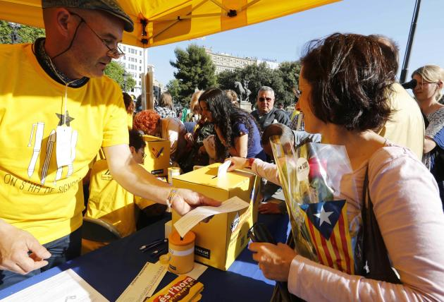 A woman cast her ballot at a Catalan National Assembly stand during Sant Jordi's day celebrations in Barcelona
