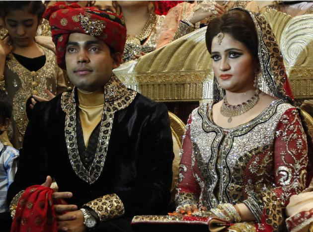 Pakistani cricketer Umar Akmal sits with his bride Noor Amna during their wedding reception in Lahore