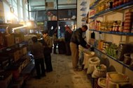 Customers shop by candlelight in a grocery store on the main street of the Aleppo neighbourhood of al-Fardos on December 9, 2012. Residents of Aleppo have suffered through months of brutal urban warfare and now face a humanitarian crisis with a lack of food and fuel as the Syrian winter sets in