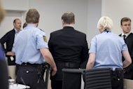 "Norwegian killer Anders Behring Breivik (centre) is escorted out of court by police in Oslo. Proceedings were briefly halted when a family member of one of Breivik's victims threw a shoe at him, screaming ""you killer, go to Hell!"""