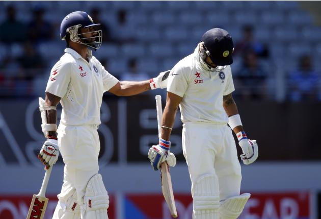 India's Shikhar Dhawan consoles Virat Kohli after he was dismissed during his second innings on day four of the first international test cricket match against New Zealand at Eden Park in Auckland