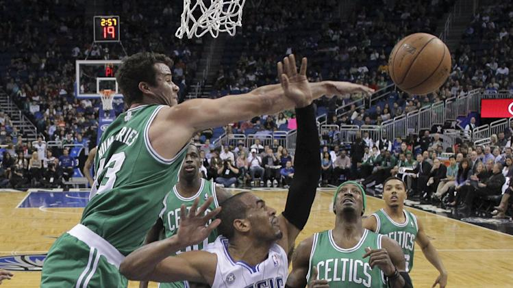 Boston Celtics' Kris Humphries, left, blocks a shot by Orlando Magic's Arron Afflalo (4) as Gerald Wallace (45) looks on during the first half of an NBA basketball game in Orlando, Fla., Sunday, Jan. 19, 2014