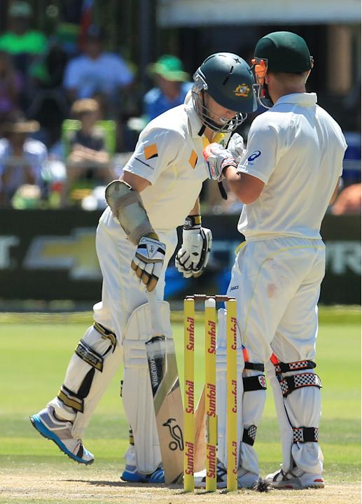 Australia's batsman Chris Rogers, left, has a word with teammate David Warner, right, on the fourth day of their second cricket test match against South Africa at St George's Park in Port Eliz