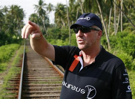 Former England cricket player Ian Botham gestures as he talks about the train that was pushed off the tracks by the December 2004 tsunami in Paraliya