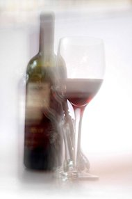 A bottle of wine and a glass are shown in a blurry photo.