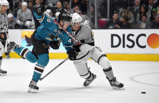 San Jose Sharks center Tomas Hertl, left, of the Czech Republic, battles with Los Angeles Kings defenseman Drew Doughty during the first period of an NHL hockey game, Saturday, April 11, 2015, in Los Angeles. (AP Photo/Mark J. Terrill)