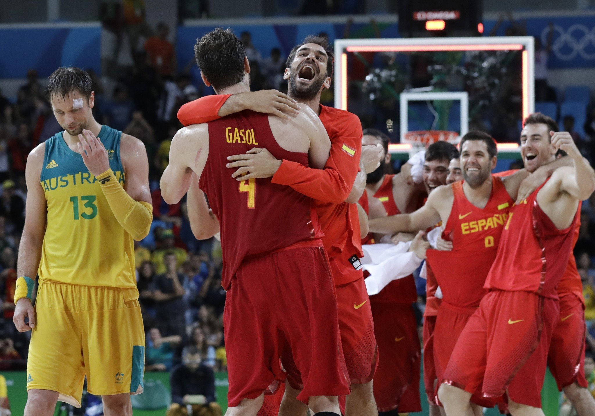 Australia's David Andersen (left) walks off the court as Spain's Pau Gasol and Jose Calderon celebrate their bronze-medal win at the 2016 Summer Olympics in Rio de Janeiro, Brazil. (AP/Eric Gay)