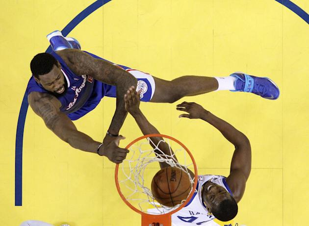 CORRECTS BYLINE - Los Angeles Clippers' DeAndre Jordan, top, dunks over Golden State Warriors' Harrison Barnes during the first half in Game 3 of an opening-round NBA basketball playoff series