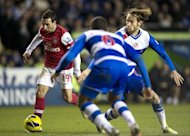Arsenal's Santi Cazorla (L) runs past Reading's Kaspars Gorkss (R) during their English Premier League match at Madejski Stadium in Reading, on December 17, 2012. Buoyed by 5-2 rout at Reading, Arsenal kick off the weekend programme at home to third-bottom Wigan Athletic on Saturday, when victory would provisionally propel them up to third place