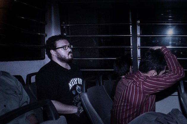 British banker Rurik Jutting (L), charged with the grisly murders of two women, sits in a prison van as he arrives at the eastern court in Hong Kong on November 24, 2014